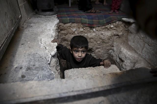 Un jeune Syrien se réfugie à l'intérieur d'un... (AFP, Sameer Al-Doumy)