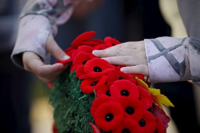Des gens épinglent leur coquelicot pendant la cérémonie... (La Presse Canadienne)