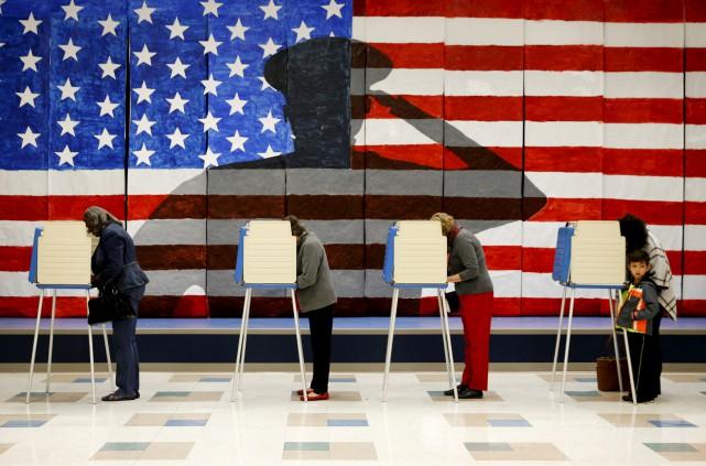 Des électeurs remplissent leur bulletin dans une école... (AP)
