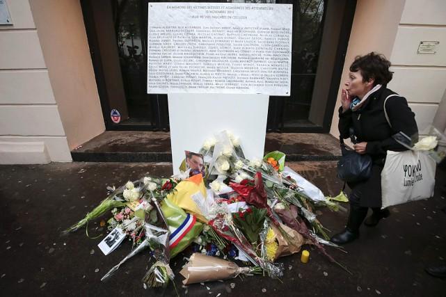 Une femme se recueille devant la plaque en... (PHOTO JOEL SAGET, AFP)
