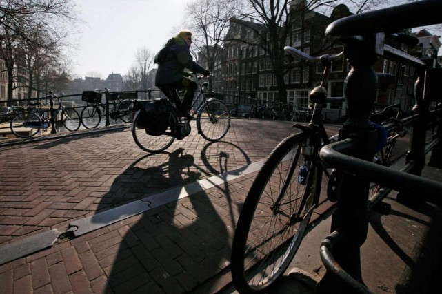 Un cycliste passe au-dessus du canal Brewers à... (Photo Peter Dejong, Associated Press)