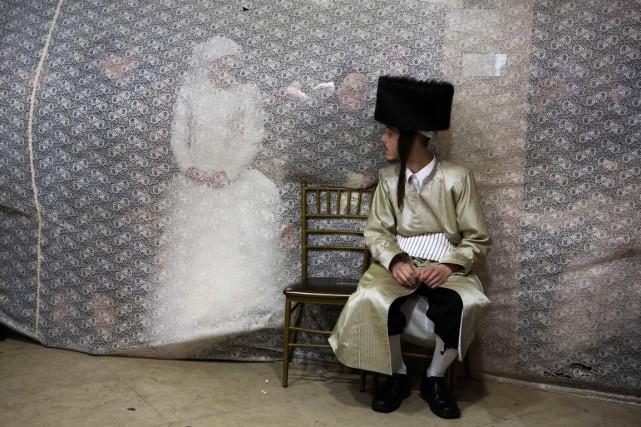 Une jeune mariée regarde son mari à travers... (photo MENAHEM KAHANA, archives AFP)