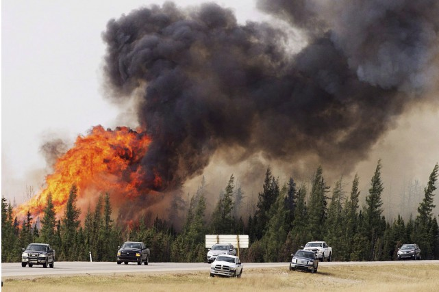 L'incendie a pris naissance dans un secteur forestier... (La Presse Canadienne)