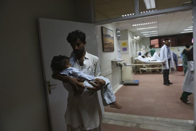 Un père transporte son enfant soigné à la... (AFP)