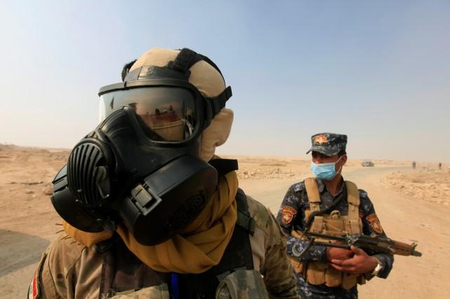Des soldats des forces irakiennes portent des masques... (photo Alaa Al-Marjani, archives REUTERS)