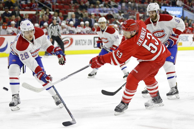Jeff Skinner tente de tirer malgré l'intervention de... (Photo AP)