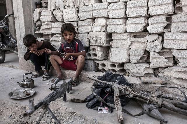 Deux enfants regardent des armes saisies auprès du... (PHOTO YASIN AKGUL, AFP)