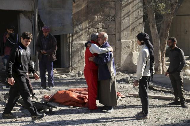 Des Syriens se consolent après un bombardement.... (AFP)