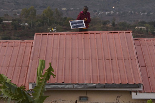 Un homme ajuste un panneau solaire sur le... (AFP, Tony Karumba)