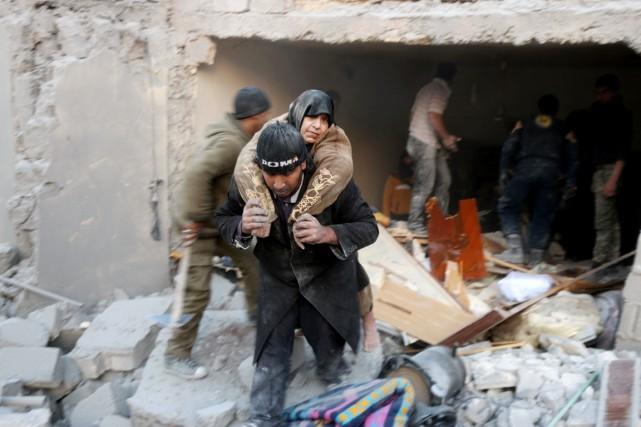 Un homme porte secours à une femme qu'il... (photo THAER MOHAMMED, AFP)