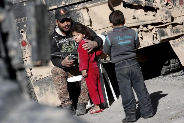 Un soldat des forces irakiennes réconforte une fillette... (AFP, Thomas Coex)