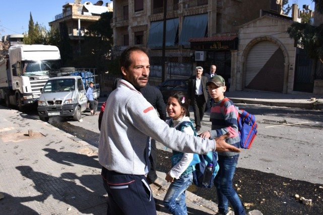 Un homme évacue des enfants d'une école à... (PHOTO GEORGE OURFALIAN, AGENCE FRANCE-PRESSE)