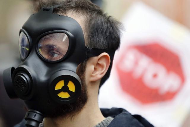 Un activiste porte un masque à gaz alors... (photo Frank Augstein, archives AP)