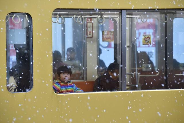 Un garçon observe la neige à travers la... (AFP)