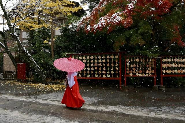 Une femme marche sous la neige à Kamakura,... (AP)
