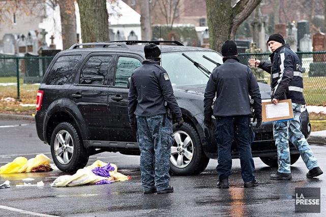 Des policiers inspectent levéhicule utilitaire sport noir qui... (Photo Patrick Sanfacon, La Presse)