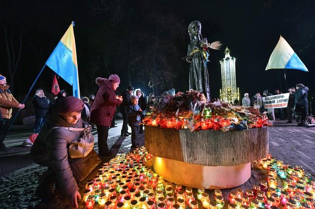 Des chandelles et des fleurs ont été déposées... (PHOTO SERGEI SUPINSKY, AFP)
