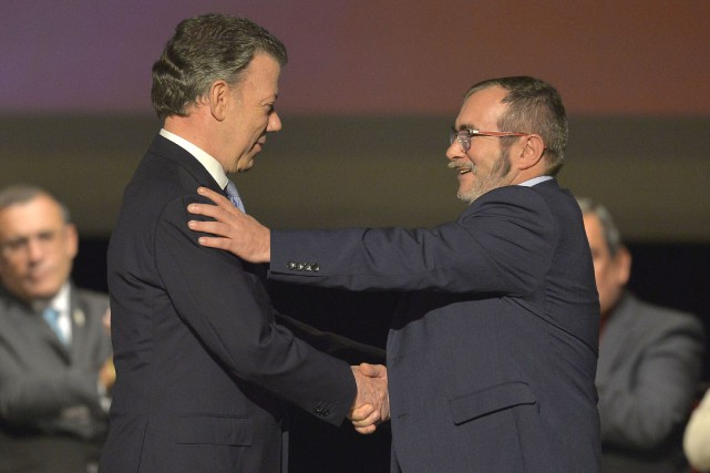 Le président colombien Juan Manuel Santos fait l'accolade... (PHOTO LUIS ROBAYO, ARCHIVES AFP)