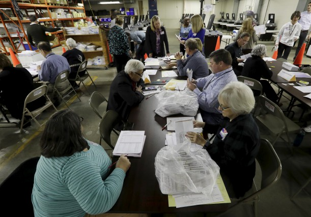 Des travailleurs commencent le recomptage à Milwaukee.... (AP)