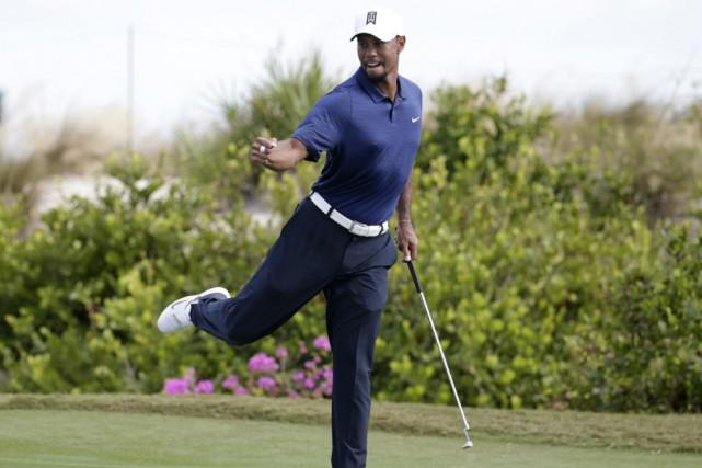 Tiger Woods célèbre après avoir sauvé la normale... (Associated Press)