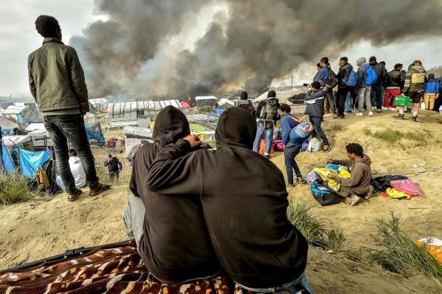 Des migrants regardent de la fumée s'échappant de... (AFP)