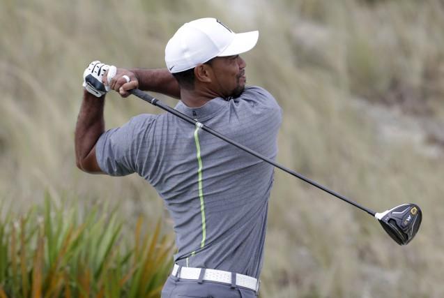 Tiger Woods observe son coup au troisième trou.... (AP)