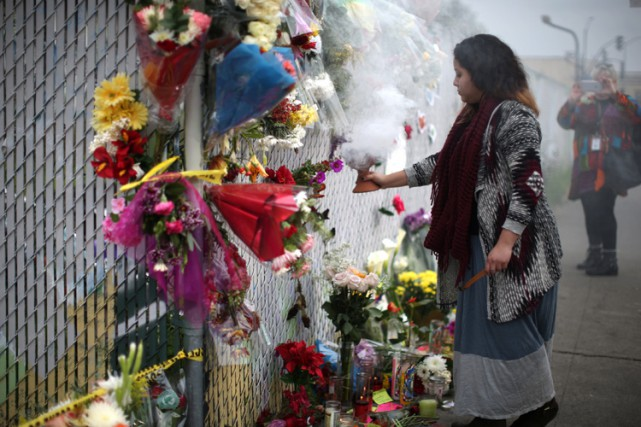 Une femme se recueilledevant un mémorial installé près... (PHOTO REUTERS)