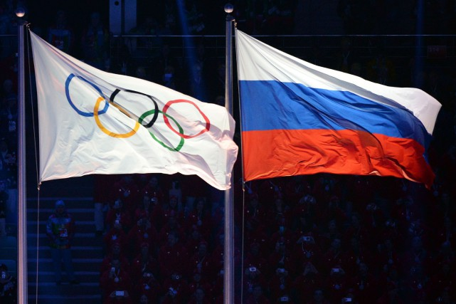 Le drapeau olympique et le drapeau russe... (Photo Yuri Kadobnov, archives AFP)