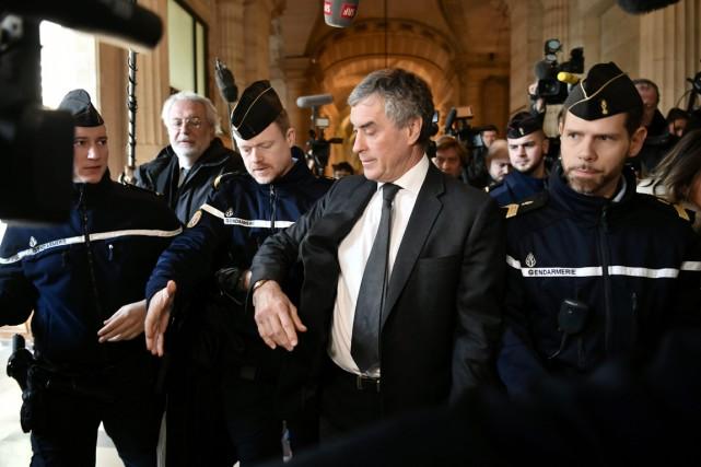 Jérôme Cahuzac (au centre) est escorté par des... (photo PHILIPPE LOPEZ, Agence France-Presse)
