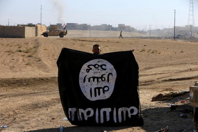 Un soldat irakien affiche un drapeau confisqué à... (PHOTO REUTERS)