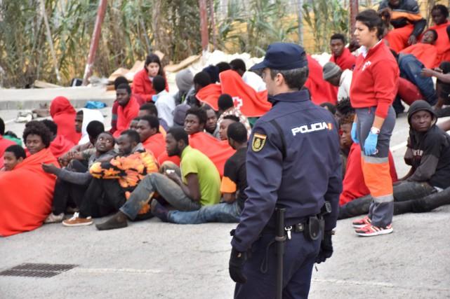 Un policier surveille les migrants qui viennent de... (AFP)