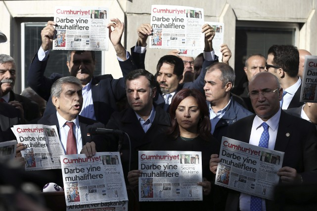 Des juristes et des journalistes exhibent des copies... (archives Associated Press)