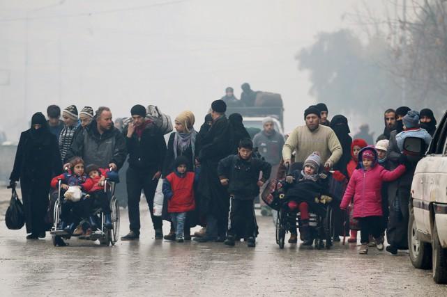 Des civils marchent alors qu'ils fuient les quartiers... (photo Abdalrhman Ismail, REUTERS)