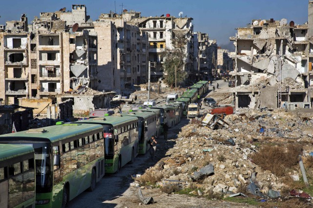 Un long convoi d'ambulances et d'autobus verts a... (AFP, KARAM AL-MASRI)