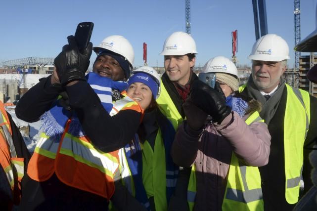 Des travailleurs prennent des égoportraits avec Justin Trudeau... (La Presse Canadienne, Ryan Remiorz)