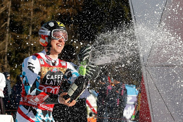 Marcel Hirscher a célébré sa victoire au champagne.... (Photo Marco Trovati, AP)