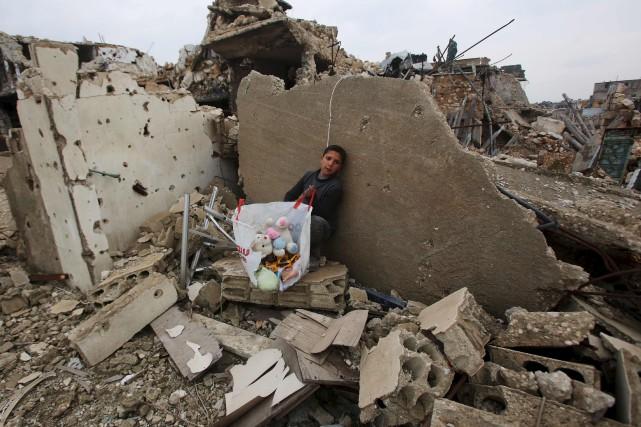Un garçon d'Alep est assis dans les ruines... (AFP, Youssef Karwashan)