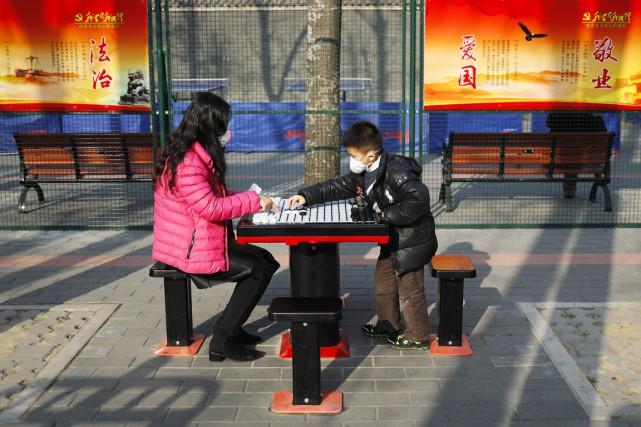 Un enfant et une femme, tous deux portant... (photo Andy Wong, Associated Press)