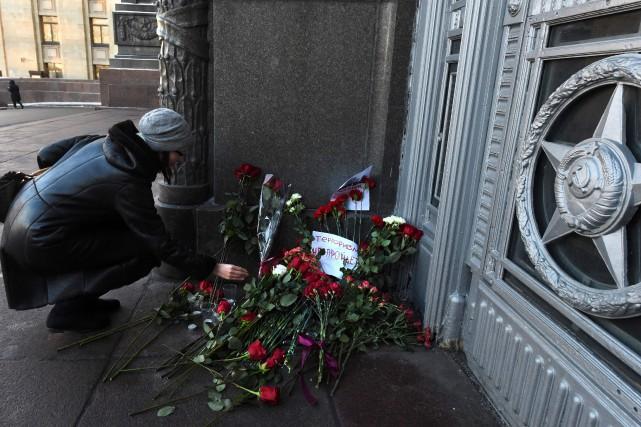 Une femme dépose des fleurs devantl'ambassade de Russie... (AFP)