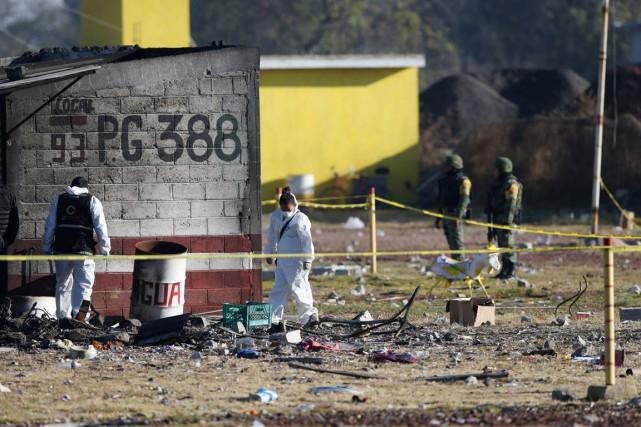 Des enquêteurs et médecins légistes arpentent les décombres... (photo Edgard Garrido, REUTERS)