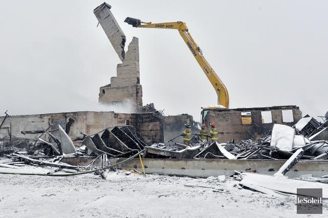 Une pelle mécanique s'affaire à démolir les ruines... (Le Soleil, Patrice Laroche)