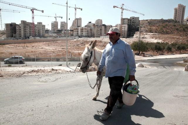 Un Palestinien marche dans le quartier de Har... (AP)