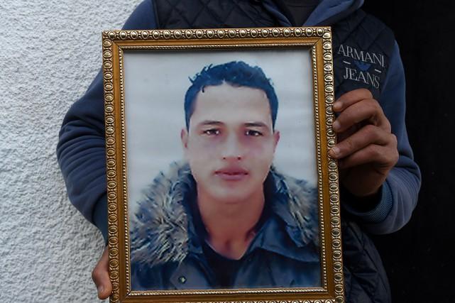 Walid Amri tient une photo de son frère... (PHOTO FETHI BELAID, AFP)
