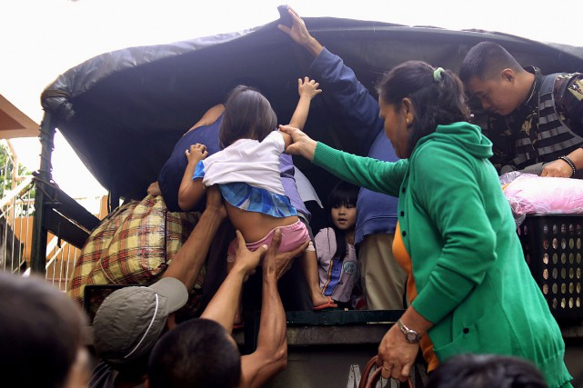 Des résidants sont évacués dans un camion militaire... (AFP)