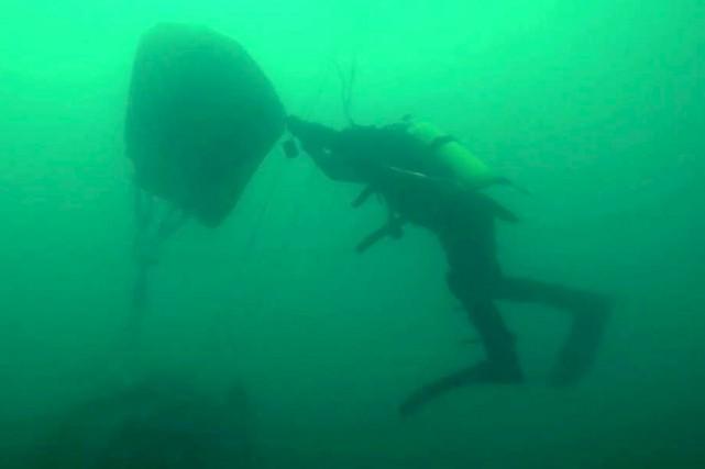 Un plongeur récupérait mercredi un débris du Tupolev... (AFP)