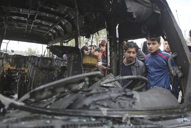 Des citoyens de Bagdad inspectent la scène après... (AP, Karim Kadim)