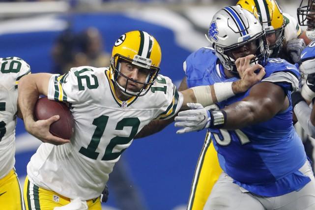 Le quart-arrière des Packers Aaron Rodgers repousse le... (Associated Press)
