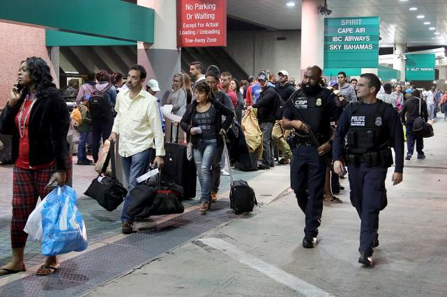 Des passagers patientent en ligne au terminal4 de... (Photo AP/Mike Stocker, South Florida Sun-Sentinel)