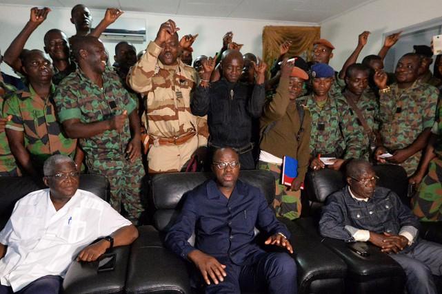 Des soldats mutins se tiennent derrière le ministre... (PHOTO SIA KAMBOU, AFP)