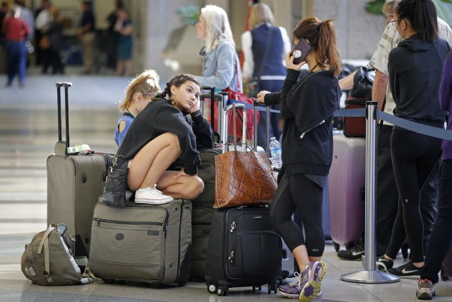 Des passagers attendent leur vol à l'aéroport international... (Photo Al Diaz /Miami Herald via AP)